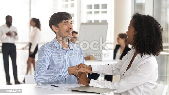 istock Caucasian male handshaking african female satisfied by good work result 1139630495