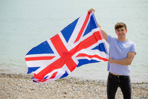 Kaukasischer Rüde an einem Strand mit britischer Flagge – Foto