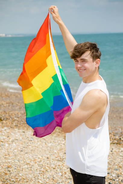 Kaukasischer Rüde an einem Strand mit einer Pride-Flagge – Foto