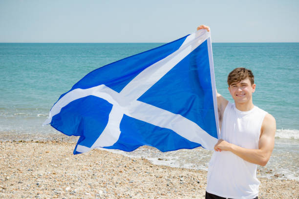 Caucasian male on a beach holding a Scottish flag stock photo