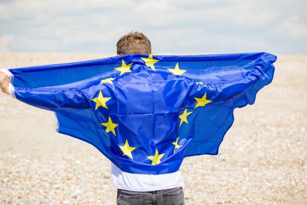 Kaukasischer Rüde an einem Strand mit einer EU-Flagge – Foto