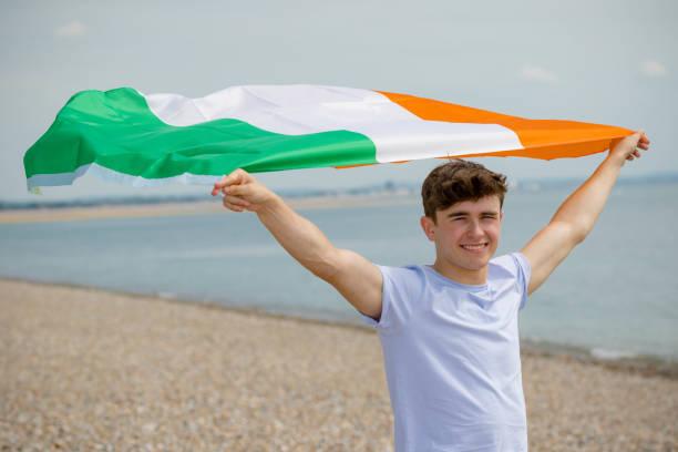 Kaukasischer Rüde an einem Strand mit irischer Flagge – Foto