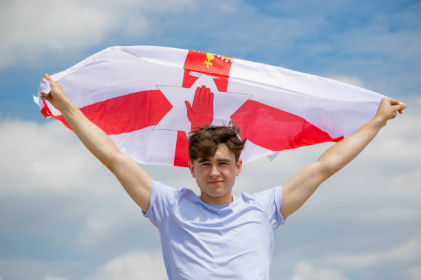 Kaukasischer Rüde an einem Strand mit Ulster-Fahne – Foto