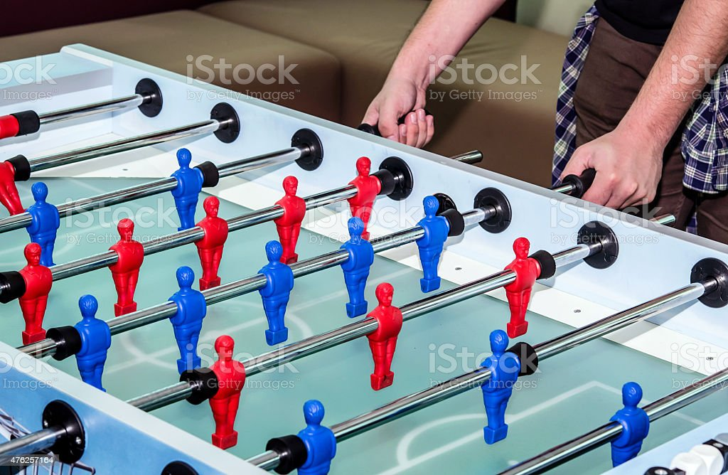 caucasian male playing table soccer football game stock photo