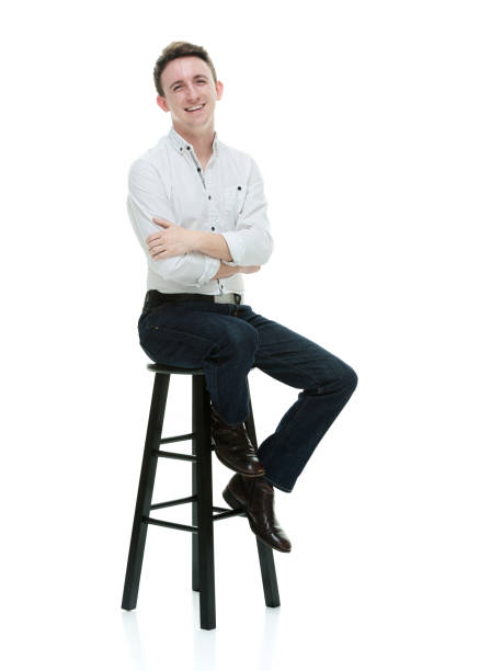 Caucasian male resting in front of white background wearing button down shirt stock photo