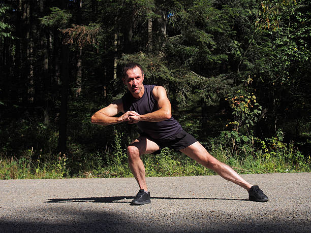 caucasian male runner athlete stretching outdoors in forest - lunge stock photos and pictures