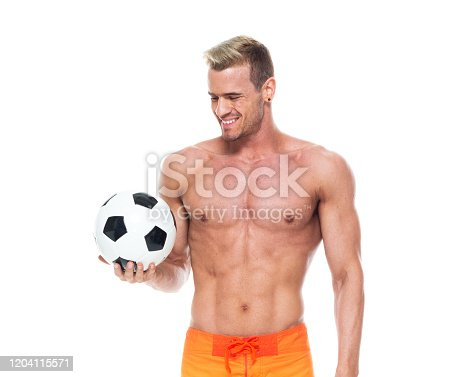 istock Caucasian male soccer player standing wearing board shorts and holding soccer ball 1204115571