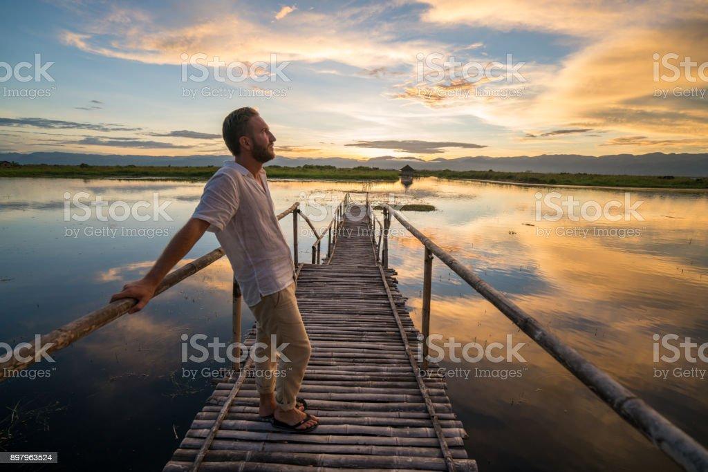 Kaukasische Männer stehen auf hölzernen See Pier betrachtet Sonnenaufgang, Myanmar – Foto
