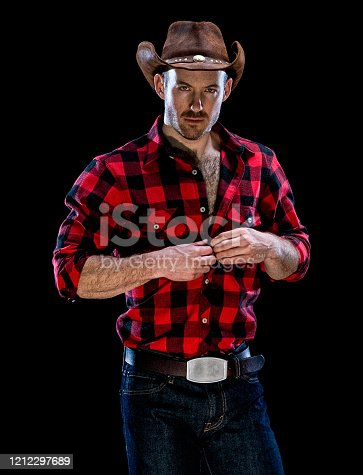 Portrait of aged 30-39 years old caucasian male stripper standing in front of black background wearing button down shirt who is of muscular build who is undressing