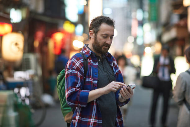 Caucasian Male Tourist Navigating Tokyo With Smart Phone stock photo