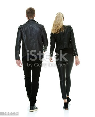 Rear view of aged 20-29 years old who is tall person with long hair caucasian male walking in front of white background wearing leather jacket who is showing cool attitude