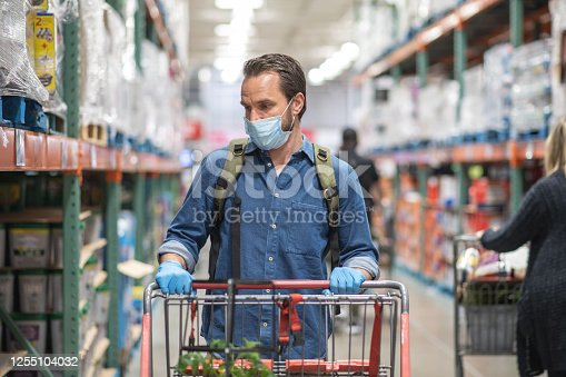 Caucasian man wears protective face mask and gloves as he shops at a local warehouse during the pandemic. He is pushing a grocery cart.