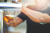Part of Caucasian man's arm with chain pouring a craft beer into a plastic cup from a tap selective focus Stellenbosch South Africa