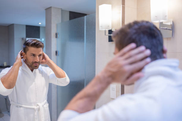 Caucasian man after shower styling his hair in the bathroom stock photo