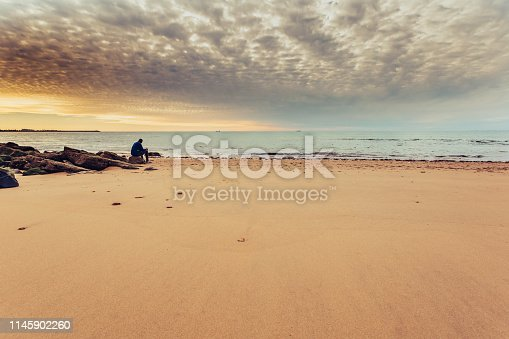 Caucasian man alone sitting on the shore of the sea, contemplating the sunset. Thoughts and loneliness of a man on the beach