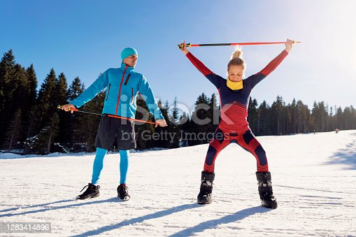 Caucasian ethnicity, young man and woman doing exercises with a ski pole at the mountain. They are enjoying beautiful, sunny mountain day and preparing for skiing.