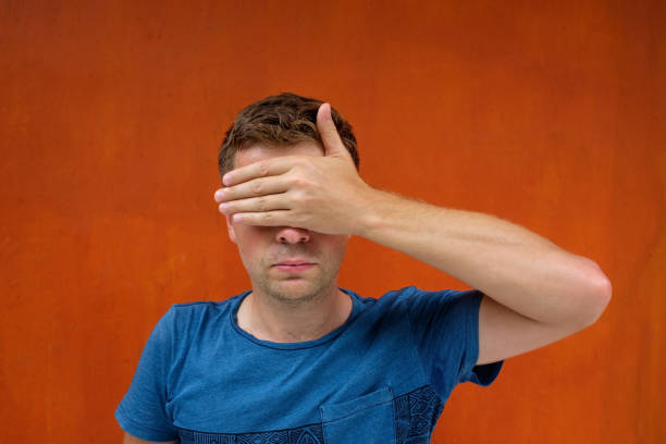 l'homme caucasien ferme les yeux avec ses mains. il ne veut pas voir quelque chose et être un témoin. - cosmetique store photos et images de collection