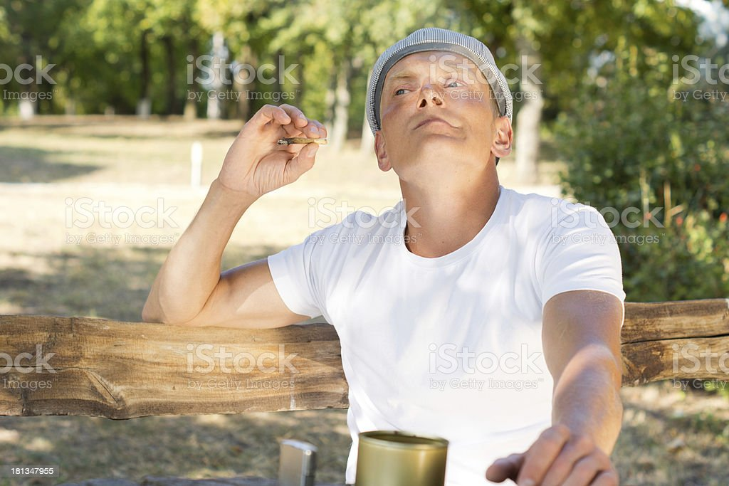 Caucasian man enjoying a rolled cigarette royalty-free stock photo
