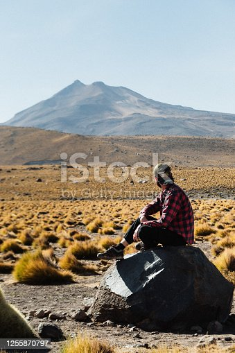 Young Caucasian traveler sitting on the rock looking on the volcano and enjoying the landscape of colors of Atacama desert in a beautiful day in El Tatio geyser valley in Chile