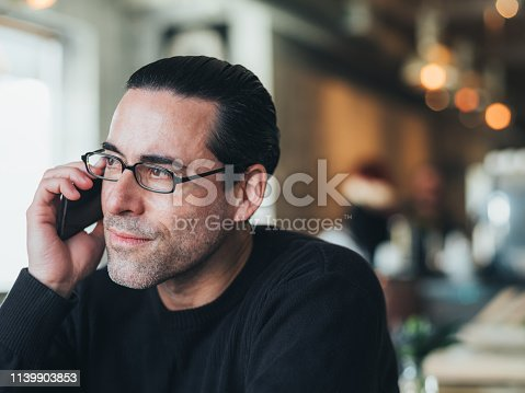 Mid adult Caucasian man having a coffee break at the local city bistro.