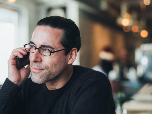 homme caucasien ayant un café au petit bistro - écouteurs intra auriculaires photos et images de collection