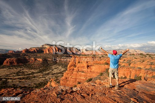 A hiker in Sedona, Arizona. Doe Mountain Trail. Middle Aged Caucasian male with arms raised against a dramatic sky. Self Portrait. Additional themes include backcountry, adventure, eco tourism, trail running, exercise, fitness, health, healthy living, recreation, leisure, one man, back view, and happiness.