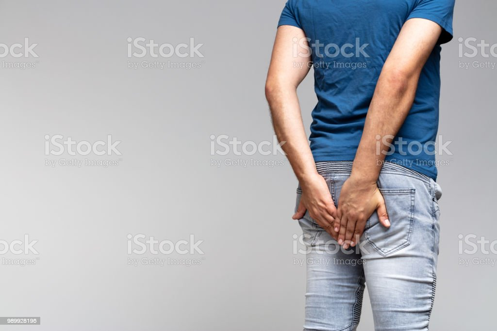caucasian man holding his buttocks in denim jeans - foto stock