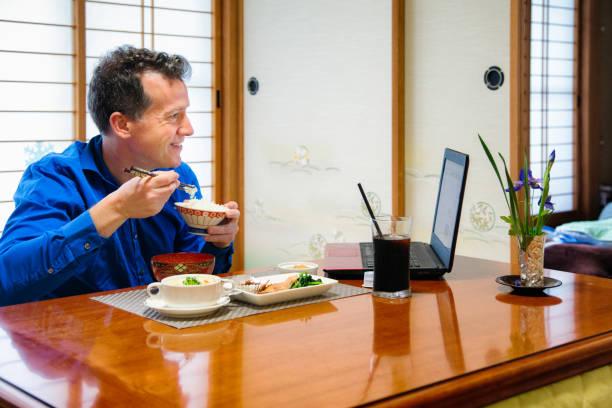 kaukasischen mann in seinem japanischen zimmer frühstücken und lächelnd auf laptop - raumteiler weiß stock-fotos und bilder