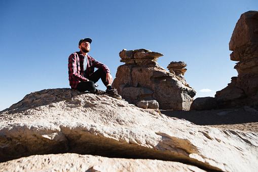 Caucasian man in looking at scenic view of El Árbol De Piedra in Altiplano, Bolivia
