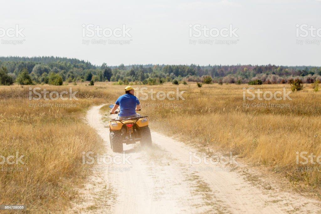 Caucasian man in sport protective goggles riding an ATV quad bike...