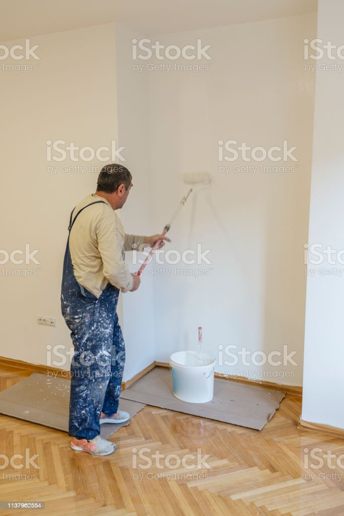 Adult Manual Worker with Paint Roller on the Stick is Busy Decorating...