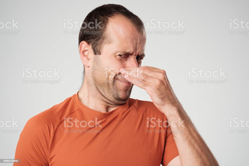 Caucasian man is pinching nose with fingers and looking with disgust because of bad smell isolated on white background stock photo