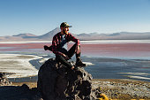 istock Caucasian man is sitting and looking at scenic view of Laguna Colorada in Altiplano, Bolivia 1298992805