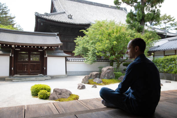 Caucasian man looking at temple garden Caucasian man looking at temple garden cross legged stock pictures, royalty-free photos & images