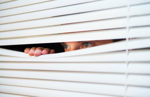 caucasian man looking through the slats of a blind - conspiracy стоковые фото и изображения