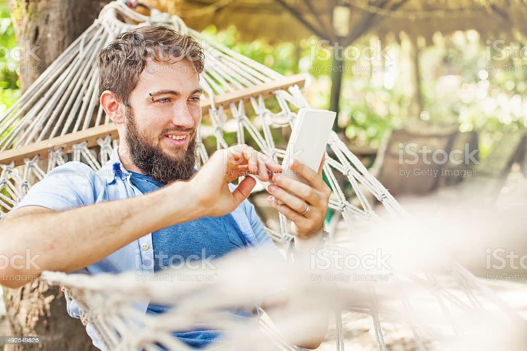 Caucasiano homem deitado na rede com telefone celular - foto de acervo