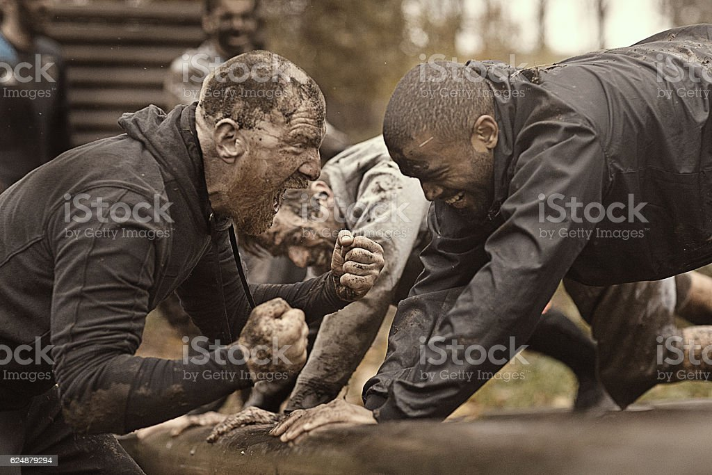 Caucasian man personal trainer coaching mud run team of men stock photo
