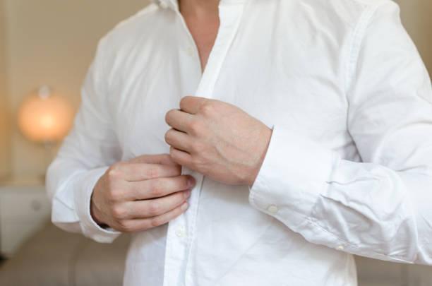 Homem caucasiano veste camisa de linho branco com luz de fundo - foto de acervo