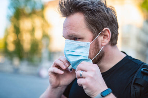 Caucasian Man Putting On Face Mask In The City stock photo