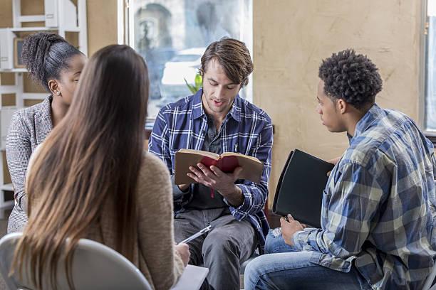 caucasian man reads bible with study group - geführtes lesen stock-fotos und bilder