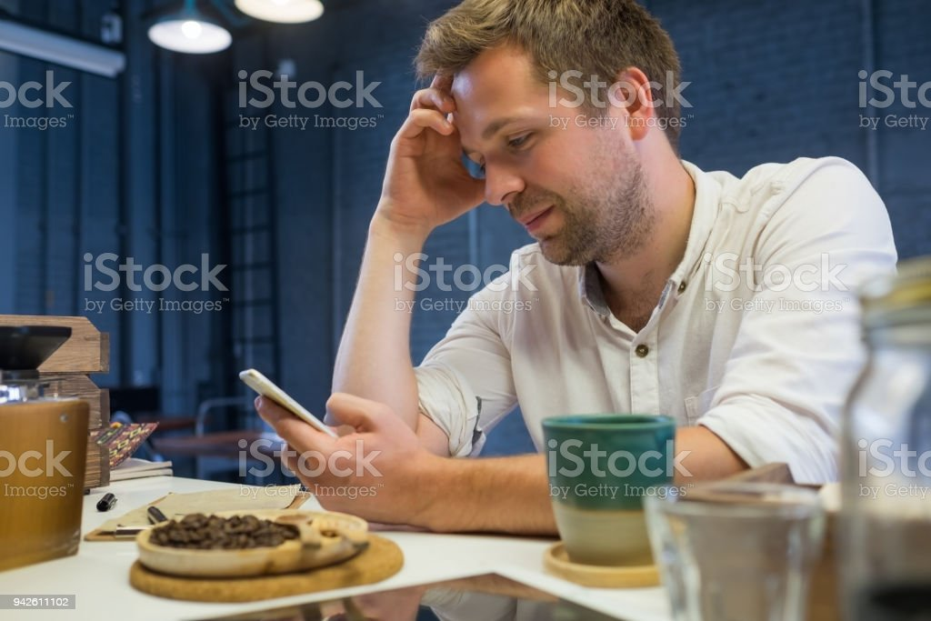 Caucasian man sitting alone in cafe and waiting his friends. stock photo