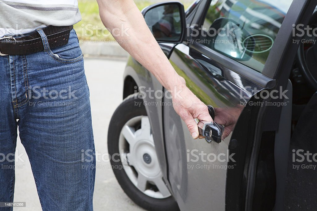 Caucasian man standing near car and holding door handle royalty-free stock photo