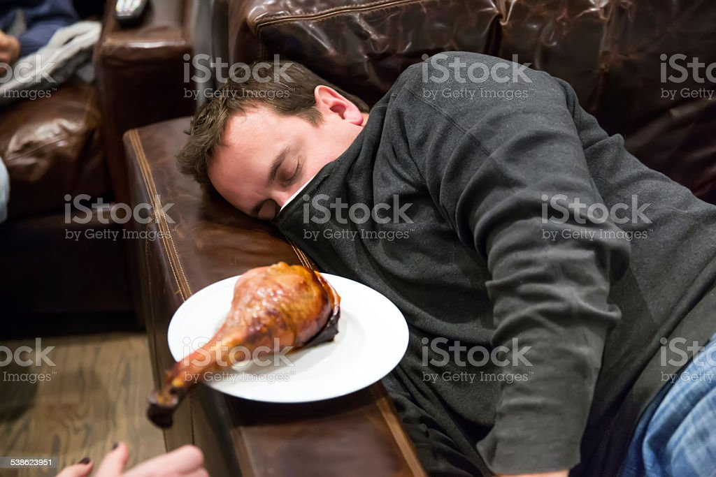 Caucasian man takes nap in a comfortable leather chair stock photo