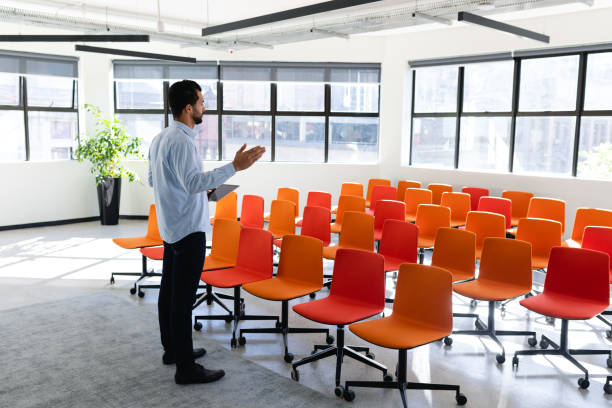 Caucasian man training himself in a conference room Side view of a Caucasian businessman wearing smart clothes, standing in an empty modern meeting room, training himself before a conference practicing stock pictures, royalty-free photos & images