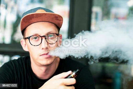 Young European man looking at the camera and smoking vapor