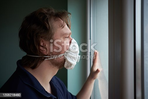 Caucasian man wearing protective medical mask looking out the window during quarantine