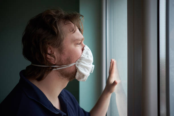 caucasian man wearing protective medical mask looking out the window during quarantine - quarantena foto e immagini stock