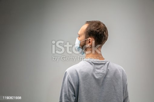 istock Caucasian man wearing the respiratory protection mask against air pollution and dusk on grey studio background 1190821938