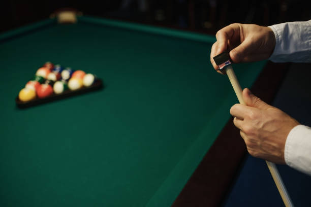 caucasian man wipes a cue with chalk ready to start game. - pool cue stock photos and pictures
