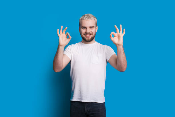 Caucasian man with blonde hair and nice beard is gesturing the approbation sign while posing in a white t-shirt on a blue wall Caucasian man with blonde hair and nice beard is gesturing the approbation sign while posing in a white t-shirt on a blue wall approbation stock pictures, royalty-free photos & images